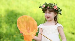 Little girl in white holds orange butterfly net on green meadow Stock Footage
