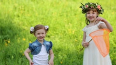 Little girl holds orange butterfly net and other girl stands near Stock Footage