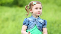 Close-up view of face of little smiling girl on green meadow Stock Footage