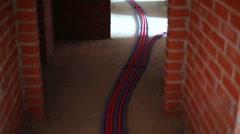 Empty corridor with walls of bricks, plastic waterpipes on floor. Stock Footage