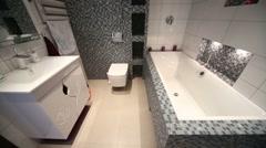 Interior of full bathroom with bath, washbasin, toilet bowl - stock footage