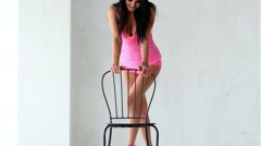 Erotic show with chair by brunette woman in white interior. - stock footage