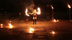 Girl moves with burning fans and boy rotates flaming pois - stock footage