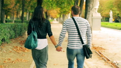 Couple walking in park and holding hands at autumn, steadycam shot Stock Footage