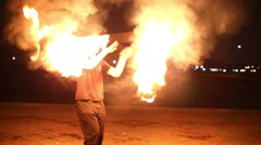 Guy juggles burning rod spinning and rotating it around body. Stock Footage