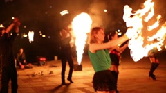 Three girls dance with flaming torches made in shape of fans Stock Footage