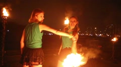 Two girls perform with burning torches at evening fire show. Stock Footage