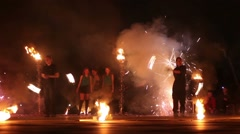 Boys move synchronously rotating burning pois at fire show. - stock footage