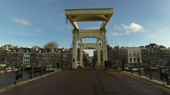 Dutch people and world travelers and cyclists pass on Skinny Bridge Stock Footage