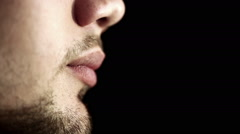 Close up profile of a young man with braces on teeth black background. Macro Stock Footage