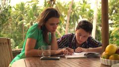 Mother helping her son doing homework by the table on terrace HD - stock footage