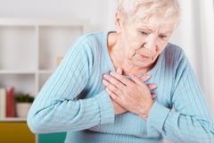 elderly woman having heart attack - stock photo