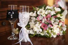Two wedding glasses and bridal bouquet on stone in summer garden Stock Photos
