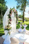 Decorated archway for wedding ceremony with colorful flowers and ribbons Stock Photos