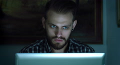 Young man using notebook computer during the night: social networks on-line Stock Footage