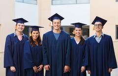 Group of smiling students in mortarboards Stock Photos