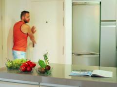 Man drinking milk in the kitchen after jogging, steadycam shot Stock Footage