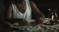 Sad man sitting alone at the table with candle lighting: sadness, loneliness Stock Footage