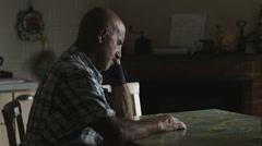 Desperate lonely man: sad man sitting alone in the kitchen  Stock Footage