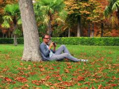 Man sitting in the park at autumn and doing photos with old camera Stock Footage