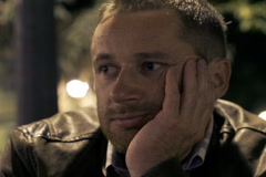 Bored man sitting in pub at night, steadycam shot Stock Footage