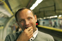 Man eating croissant and smiling to the camera in the station, steadycam shot Stock Footage