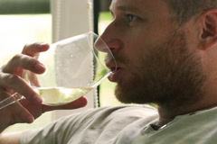 Man drinking white wine and relaxing at home Stock Footage
