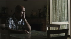 Depressed lonely man sitting at the table: sad man with problems, thoughtful Stock Footage