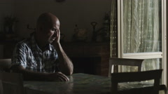 Depressed lonely man sitting alone: thoughtful, pensive, sad Stock Footage