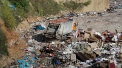 Garbage truck unloads waste on landfill Stock Footage