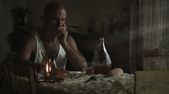 Sad man sitting alone in the kitchen with candle light: sadness, thoughtful Stock Footage
