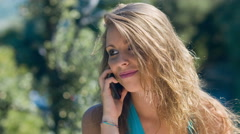 Cute blonde girl is talking at the mobile phone: smartphone, conversation Stock Footage