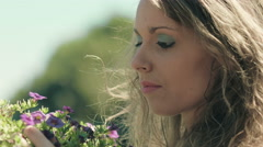 pensive girl is touching flowers: thoughtful girl with some problem in love - stock footage