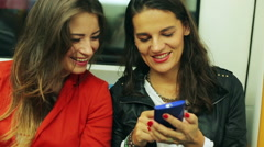 Female friends watching something on smartphone in subway, steadycam shot Stock Footage