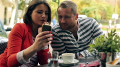 Couple watching something funny on smartphone, steadycam shot Stock Footage