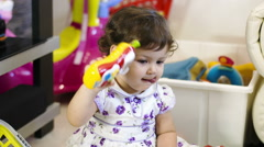 Little girl playing with her toys: having fun, laughing, enjoying  Stock Footage