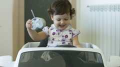 Kid playing with her toy car: little girl having fun in her house Stock Footage
