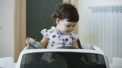Little girl playing with toy car: kid enjoying in her house with toys Stock Footage