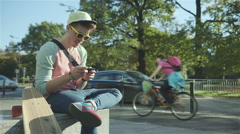 Young cheerful boy sitting on a bench and texting on a mobile phone, outdoors. - stock footage