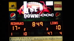 College electronic scoreboard showing 1st down - stock footage
