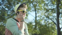 Stock Video Footage of Portrait of a stylish cheerful boy talking on phone, outdoors.
