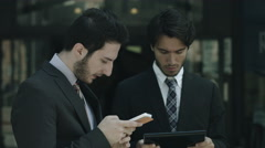 Business people using smartphone computer near office: team work, mobile phones Stock Footage