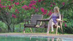 Woman Sitting thinking by swimming pool Stock Footage