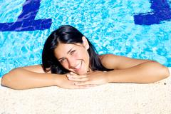 Stock Photo of beautiful female model smiling in swimming pool