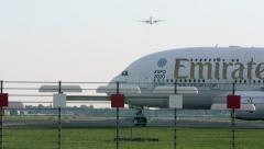 One plane is airborn, Emirates Boeing enters shot Stock Footage