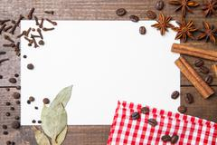 Paper for recipes and spices on wooden table Stock Photos