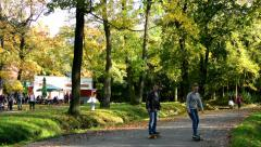 Autumn park (trees) - people walking - fallen leaves - building (restaurant) Stock Footage