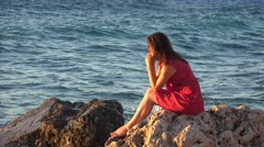 Young woman sitting on rocky seashore, long hair weaving in the breeze 4K Stock Footage