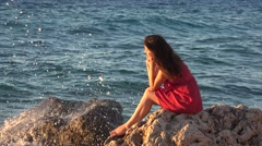 Thoughtful young woman sitting on rocky coastline, sea wave splashing 4K Stock Footage