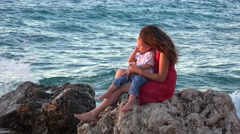 Young mother holding in arm loving child sitting on rocky seashore admiring 4K Stock Footage